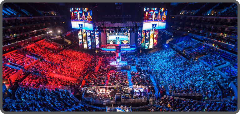An audience of gaming fans watch a live esports event in a stadium arena